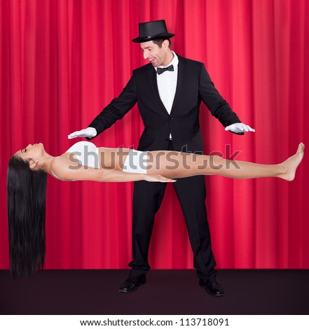Magician Performs Magic With Beauty Girls In Mid-air - stock photo