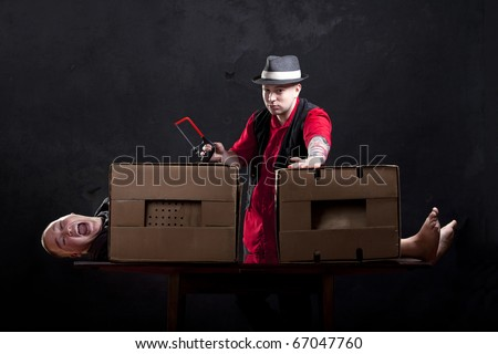 Magician sawing a man in half. - stock photo
