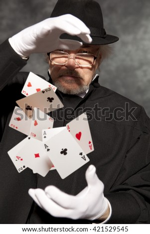 Magician show with playing cards. On grey background - stock photo