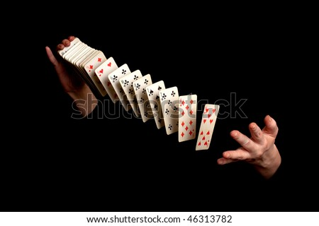 magician showing his trick with cards on black background - stock photo