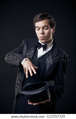 magician showing tricks with top hat isolated on dark background - stock photo