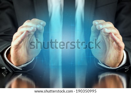 Magician with a crystal blue glow holding his hands protectively above it to feel the energy as he foretells or predicts the future conceptual of a fortune teller.  - stock photo