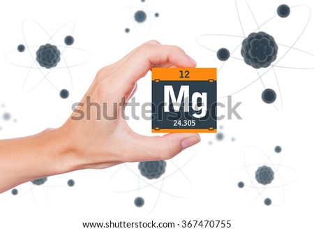 Magnesium element symbol handheld and atoms floating in background - stock photo