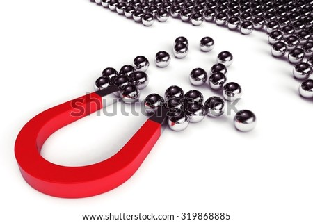 Magnet attracts steel balls from a pile - stock photo