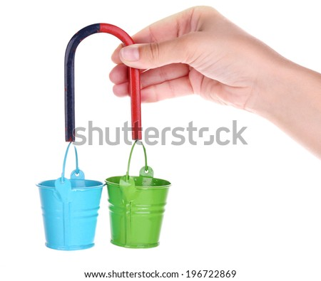 Magnet in hand holding small  iron buckets isolated on white  - stock photo
