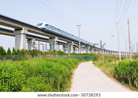 magnetic levitation (maglev) train travels at 431 km per hour through suburban shanghai, china - stock photo