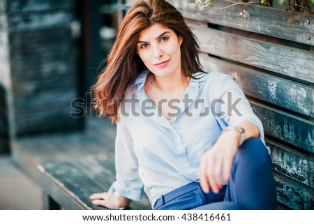 Magnificent brunette sits on bench which is on city street.