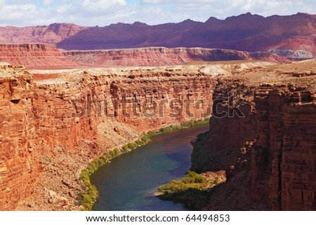 Magnificent Colorado River slowly flows into the high banks of red sandstone - stock photo