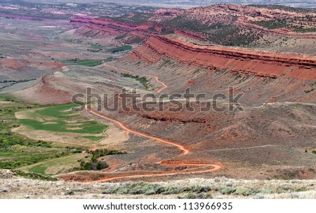 Magnificent colors of the landscape of  Elk Valley Wyoming with it's red rock formations and green valley floor. - stock photo