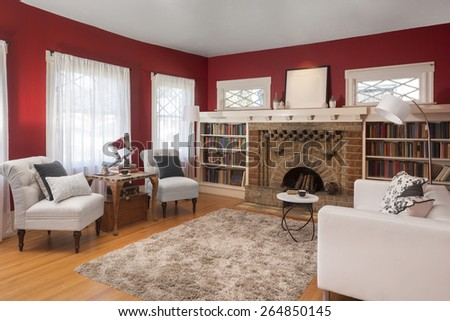 Magnificent decorated Living Room in Red with centered fire place, fitted bookshelves , designer couch with pillows, natural colored fine sisal rug, wooden floor, chair, mirror and antique camera. - stock photo