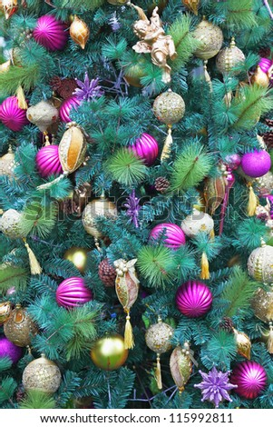 Magnificent fur-tree toys - pink and yellow glass spheres, peaks, decorative snowflakes and figures of fantastic heroes decorate a New Year tree. Happy Christmas! - stock photo