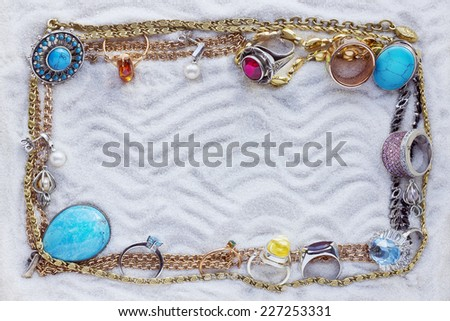 Magnificent gold chains and jewelry on white sea sand abstract  frame.  - stock photo