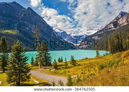 Magnificent Lake Louise is surrounded by mountain peaks and glaciers. Great sunny day. Rocky Mountains, Canada, Banff National Park - stock photo