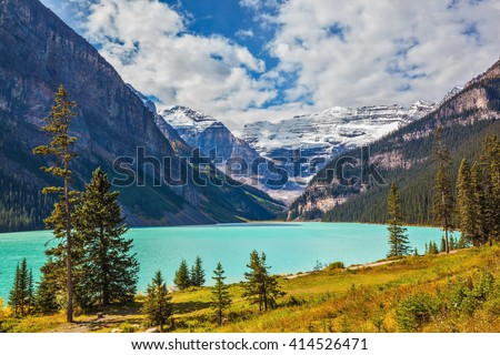 Magnificent Lake Louise is surrounded by mountain peaks and glaciers. Rocky Mountains, Canada, Banff National Park. Great sunny day - stock photo