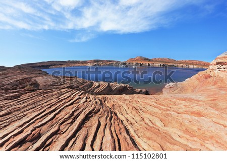 Magnificent Lake Powell. The small bay in the middle of the desert rock of red-orange striped sandstone. Photo taken fisheye lens - stock photo