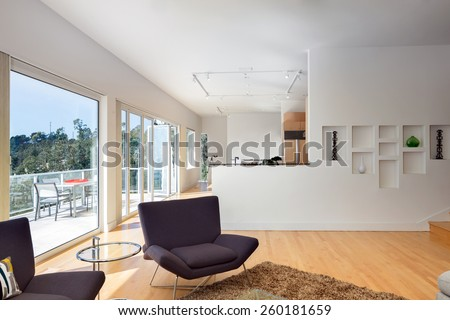 Magnificent living room in contemporary home with folding Glass Wall systems and bay view windows. Hardwood floor with hand-woven natural fine sisal rug in open space living room and fire place. - stock photo