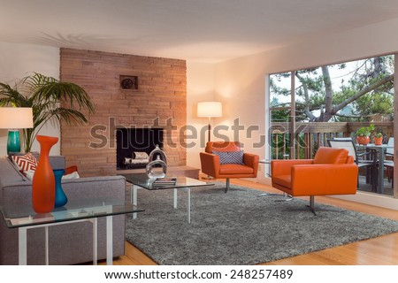 Magnificent living room interior at twilight with view window, french sliding doors and hardwood floor. Couch with hand-woven natural colored fine sisal rug open space living room within nature. - stock photo
