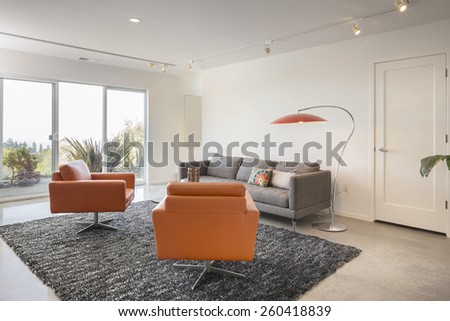 Magnificent living room interior with polished concrete floor and french sliding doors leading to outdoors. Couch with round glass table and hand-woven natural colored fine sisal rug. - stock photo
