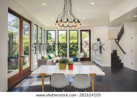 Magnificent living room interior with white table and designer chandelier in contemporary home with large windows surrounded by trees. Hardwood floor with hand-woven natural fine sisal rug. - stock photo