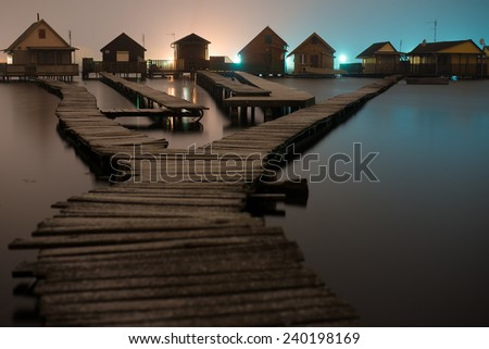 Magnificent long exposure lake at night with fishing houses - stock photo
