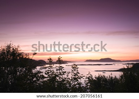 Magnificent midnight sunset over the pretty fishing town of Alesund in Norway. - stock photo
