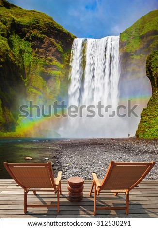 Magnificent powerful jet Sk�³gar River forms a large rainbow. The famous waterfall Sk�³gafoss, Iceland. On stony ground in front of the waterfall are two wooden deck chairs - stock photo