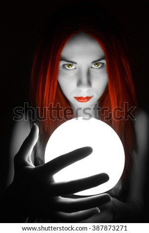 Magnificent Redhead fortune teller holding crystal ball. beautiful woman tries to look into the future - stock photo
