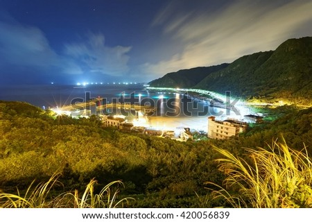 Magnificent scenery of a coastal highway along beautiful coastline and a fishing village before sunrise ~ Aerial view of a fishing village at night on northern coast of Taipei Taiwan - stock photo