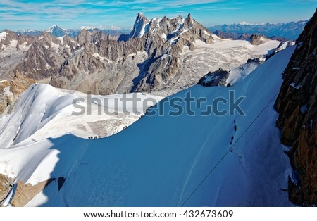 Magnificent scenery of rugged Alpine mountain peaks with view of mountaineers climbing the ice ridge and the Aiguille du Midi summit casting shadows over the glacier near Mont Blanc, Chamonix, France  - stock photo