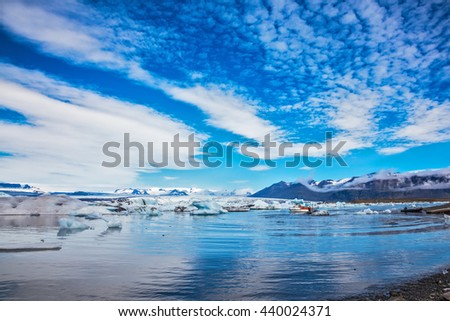 Magnificent summer morning in the ocean gulf with floating ice floes. The layered clouds fanning are reflected in a smooth surface of water. Ice lagoon in Iceland