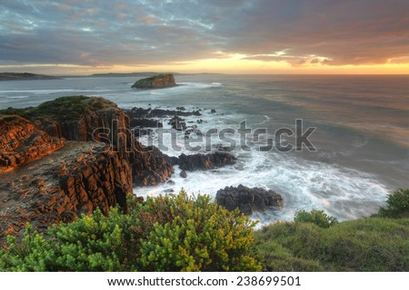 Magnificent sunrise morning and beautiful soft sunlight highlighting the rocks at Minamurra, Australia  The name Minnamurra means plenty of fish in  Aboriginal language - stock photo