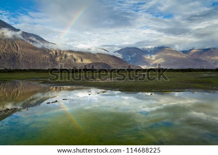 Magnificent sunset in the Nubra valley (Himalayas, India) with a rainbow after the rain. - stock photo
