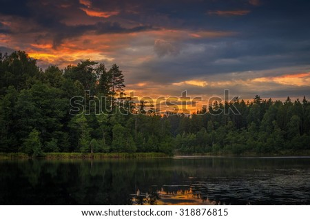 magnificent sunset over the forest lake - stock photo