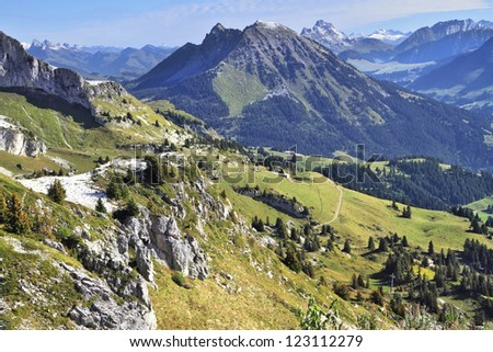 Magnificent Swiss Alps in early autumn. Green alpine meadows side by side with the first light snow - stock photo