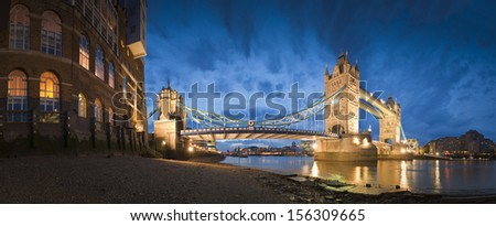 Magnificent Victorian Tower Bridge of London built in 1894 still stands as a symbol of the city. Converted brick warehouses and Thames beach and river illuminated by pretty night time lights. - stock photo