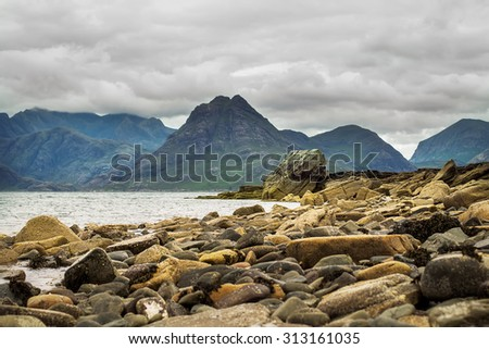 Magnificent view on Cuillin Hills  from stone beach in small Elgol village in Scotland, UK. Image with selective focus - stock photo