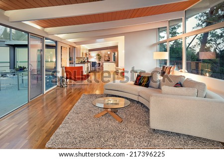 Magnificent white living room interior at twilight with view window, french sliding doors and hardwood floor. Couch with hand-woven natural colored fine sisal rug open space living room within nature. - stock photo