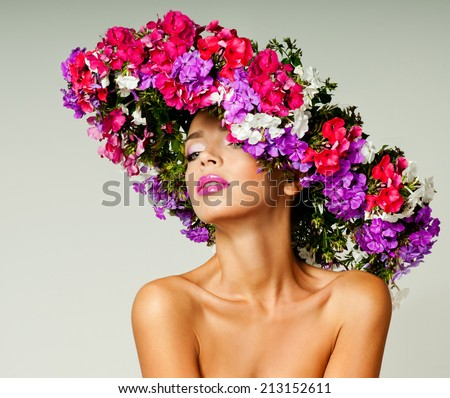 magnificent woman in a hat made of flowers - stock photo