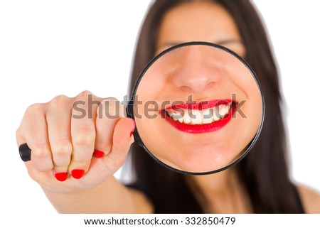 Magnified glass held by smiling woman - focus on lips. - stock photo
