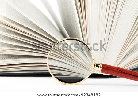 Magnifier and book closeup on the white - stock photo