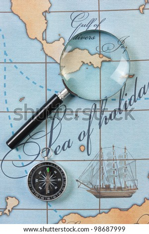 magnifier and compass on a stylized map - stock photo