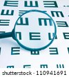 Magnifier and eyesight chart background - stock photo