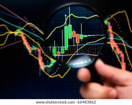 Magnifier and graph, basic tools of technical analysis on the stock market. - stock photo