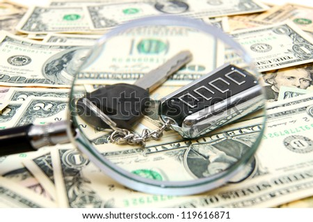 Magnifier and key from the car on banknotes. - stock photo