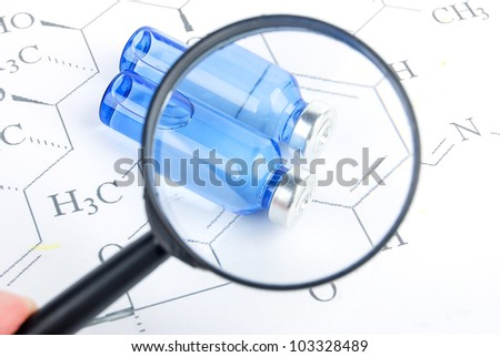 Magnifier and medicine on chemical formula - stock photo