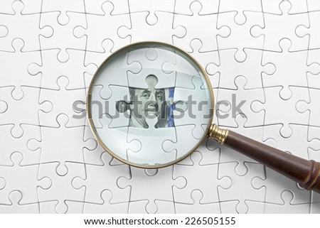 Magnifier and puzzle on money.
