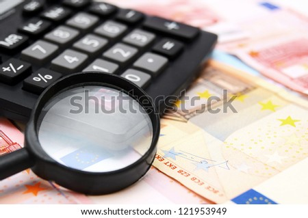 Magnifier and the calculator for euro banknotes. - stock photo