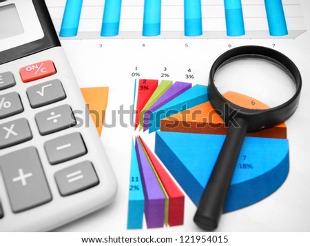 Magnifier and the calculator on graphs. - stock photo
