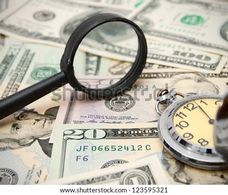 Magnifier and watches on dollars. - stock photo