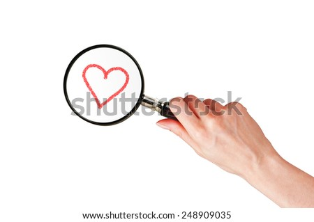 Magnifier glass in woman hand and red heart isolated on white background - stock photo